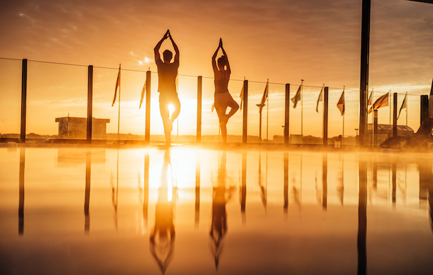Yoga am Pool bei Abenddämmerung