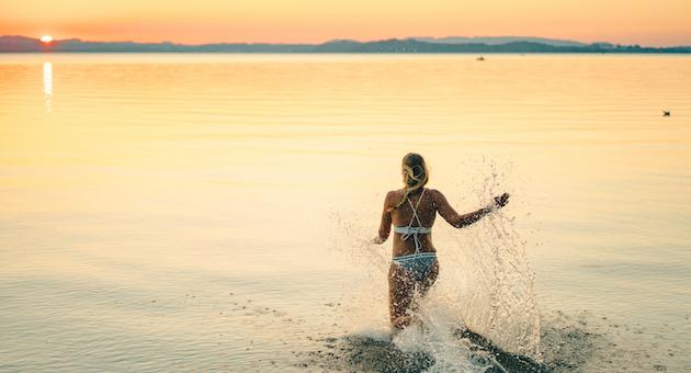 Frau läuft ins Wasser
